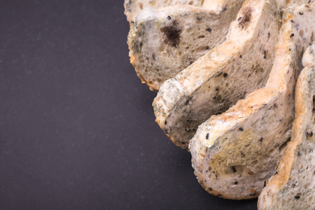 Mold on bread put on black stone table background. Top view Фото со стока
