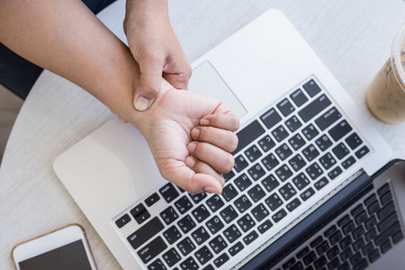 Close up woman holding and pressing or touching her wrist while working with laptop in the office. Numbness or pain on wrist concept.
