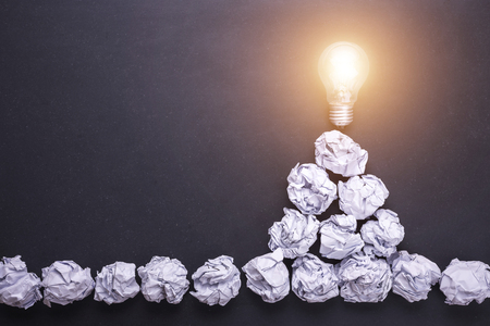 Top view crumpled white paper and light bulbs on black stone board. Create idea concept Stockfoto