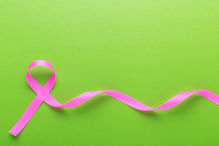 Breast Cancer concept : Pink ribbon symbol of breast cancer on green background