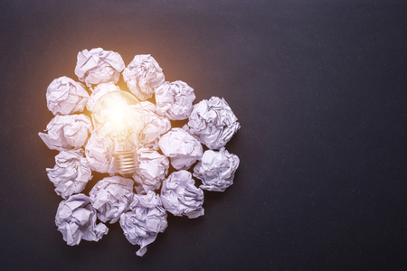 Top view crumpled white paper and light bulbs on black stone board. Create idea concept Stock Photo