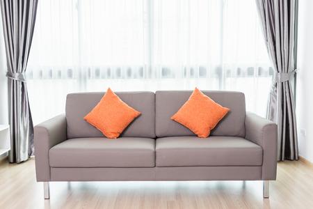 현대 거실 창 옆에 회색 소파. 홈 인테리어 장식