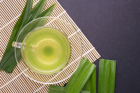 Pandan Juice in clear glass and fresh Pandan Leaves on black stone board background. Top view Stock Photo