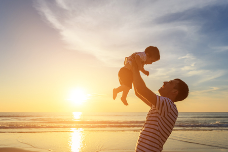 Silhouette of father playing with his son on the beach at the sunset time. Outdoor and friendly family concept