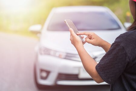 Asian woman using smartphone in front of her broken car on the road. Contacting car technician or need help concept