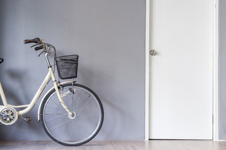 Vintage bicycle parking near the grey wall and white door