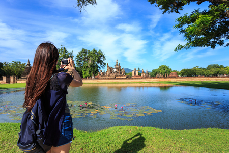 Woman tourist take a photo in Sukhothai Historical Park at Sunset time, Sukhothai province, Located in a beautiful setting of lawns, lakes and trees in north-central of Thailand Banque d'images
