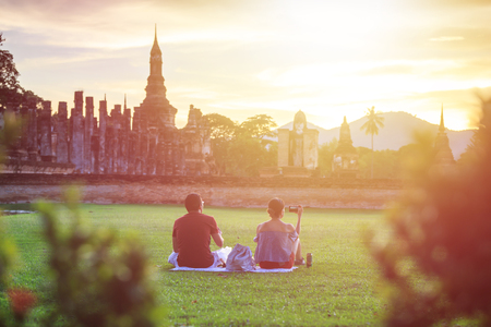 Two of tourist sitting in Sukhothai Historical Park at Sunset time, Sukhothai province, Located in a beautiful setting of lawns, lakes and trees in north-central of Thailand