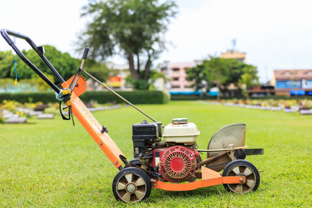A man mowing the grass in the public garden. Outdoor working