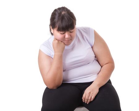 La maglietta bianca di usura di donna asiatica grassa si è preoccupata per la sua dimensione corporea isolata su fondo bianco