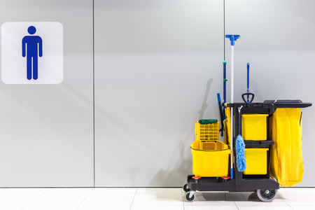 Yellow mop bucket and set of cleaning equipment and sign of men toilet on the wall in the airport