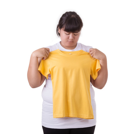 Fat asian woman trying to wear small size of yellow t-shirt isolated on white background. Fat and Healthcare concept