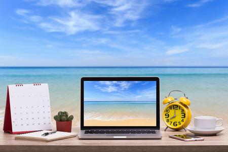 Moderne Laptop-Computer, Kaffeetasse, Wecker, Notizbuch und Kalender auf Holztisch und Ansicht des tropischen Strandhintergrundes. Standard-Bild