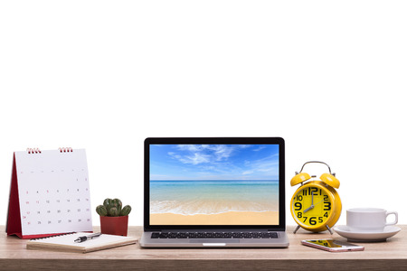 Modern laptop computer, Coffee cup, alarm clock, notebook and calendar on wooden table and view of tropical beach background. Saved with clipping path. Work and holiday concept