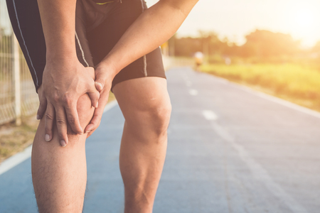 Injury from workout concept : The asian man use hands hold on his knee while running on road in the park. Shot in morning time, sunlight and warm effect with copy space for text or design