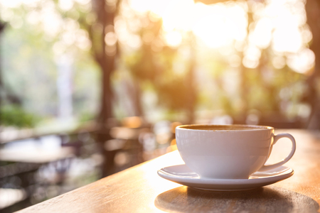 Close up white coffee cup on wooden table or counter in coffee shop and blur light bokeh background Stock Photo