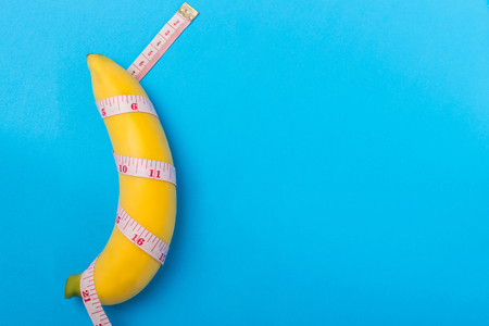 Close up yellow banana with measurement tape on blue background. Men penis size concept with empty free space for text or design. Top view Stock Photo