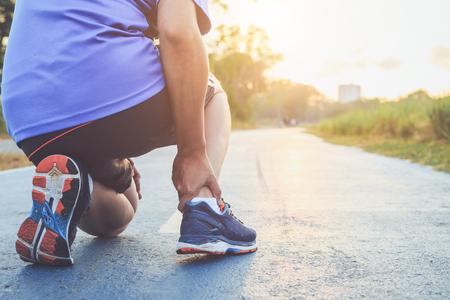 Lesión por concepto de entrenamiento: el hombre asiático usa las manos para sostener el tobillo mientras corre en la carretera del parque. Centrarse en el tobillo.