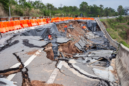 Big damage of asphalt road on the hillside cause of heavy rain and sliding earth in northern of Thailand Stock Photo