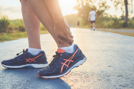 Injury from workout concept : The asian man use hands hold on his ankle while running on road in the park. Focus on ankle. Stock Photo