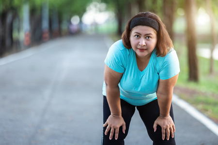 Exercise and healthy concept : Fat woman feeling tired while running in the park Stockfoto