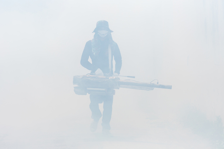 Mosquito repellent concept : A man fogging chemical to eliminate mosquito at the street 版權商用圖片
