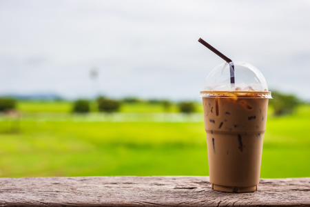 Close up iced coffee in plastic cup with drinking straw on terrace and green field background