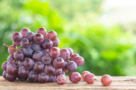 Bunch of ripe red grapes on wooden table with green space blur background