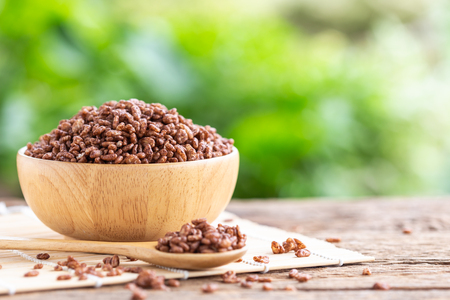 Breakfast cereal, Puffed rice with cocoa in bowl on wooden table with green blur space background for text or design. Food concept