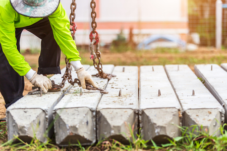 Construction worker unloading concrete stake from truck in construction site Standard-Bild