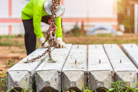 Bauarbeiter entladen Betonpfahl vom LKW auf der Baustelle Standard-Bild