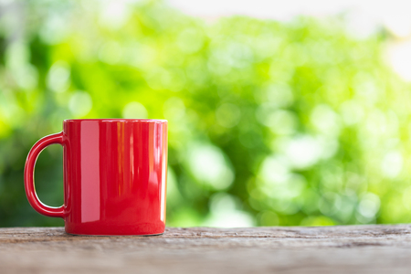 Red ceramic coffee cup on wooden table or counter with green nature light blur background and space for text, design, photo montage or advertising