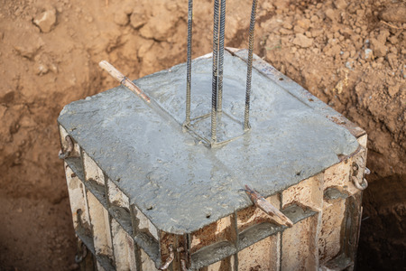 Work industrial concept : Pouring concrete into steel box for foundation pillar in process of house building