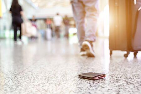 Los viajeros perdieron su billetera en el piso del aeropuerto. Perder dinero mientras viaja concepto. Centrarse en la billetera Foto de archivo