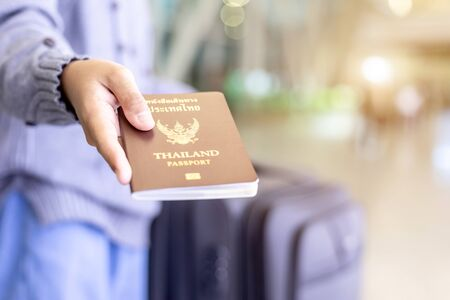 Travelers showing their Thailand passport at the airport. Checking passport while traveling concept. Focus on passport Stock Photo