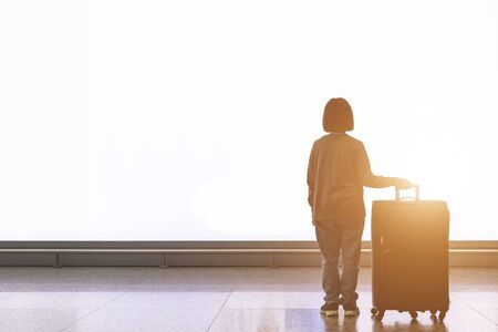 Young tourist with luggage standing in front of big white light billboard at the airport. Travel and advertising concept