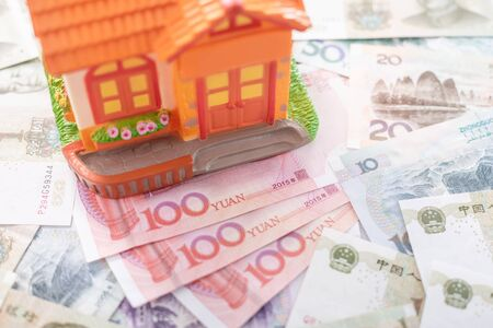 Buy or rental the house concept. Close up several banknote currency Chinese Yuan (CNY or RMB) and house model for property and land business used