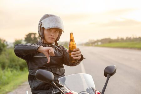 Motorcyclist sitting on his motorcycle and show hand with symbol no drinking alcohol or beer. Safe ride concept