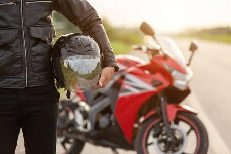 Bel motociclista indossa una giacca di pelle e tiene il casco sulla strada. Concetto di viaggio e trasporto sicuro