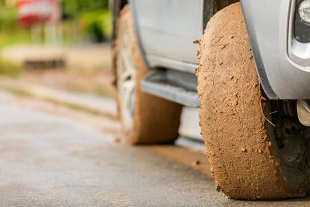Wheel of SUV car with dirty from mud and clay. Parking on the road for safe drive concept Banco de Imagens