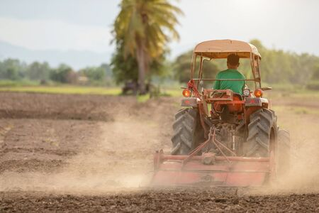 Thai farmer on big tractor in the land to prepare the soil for rice season in Thailand