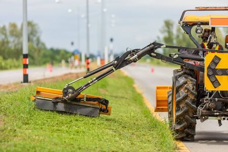 Tractor with a mechanical mower mowing grass on the side of the asphalt road. Working outdoor concept