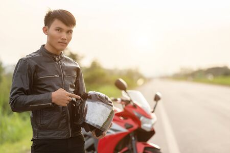 Handsome motorcyclist wear leather jacket and holding helmet on the road. Safe ride and transportation concept Zdjęcie Seryjne