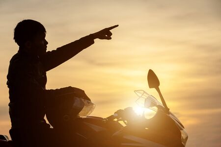 Handsome motorcyclist point the finger to the sky. Silhouette of  motorcyclist in sunset time Zdjęcie Seryjne
