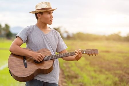 Asian man playing guitar at the green rice field in the sunset time. Countryside of Thailand Zdjęcie Seryjne