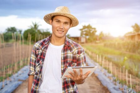 Portrait of young Asian smart farmer holding tablet in his organic farm. Technology and agriculture concept 版權商用圖片