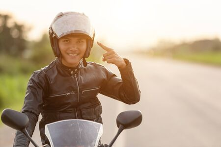 Handsome motorcyclist point the finger to his helmet. Wear the helmet before ride concept Stok Fotoğraf