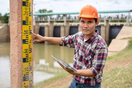 Asiatischer junger Ingenieur, der vor Ort am Damm arbeitet und den Pegel des Messgeräts an der Stange überprüft Standard-Bild