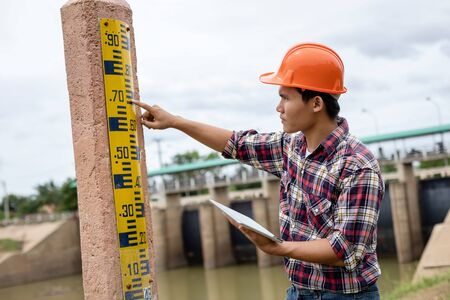 Asian young engineer working on site at the dam and checking level of gauge on the pole
