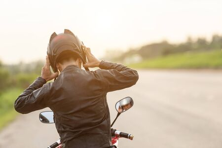 Handsome motorcyclist wear leather jacket and holding helmet on the road.
